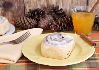 Delicious Cinnamon Bun with a glass of apple cider.