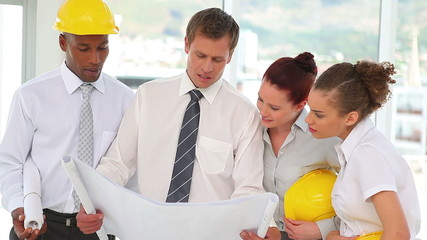 A group of construction architects looking at blueprints