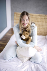 Young woman with teddy bear, smiling, portrait