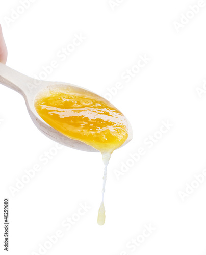 Spoon with lime honey on a white background