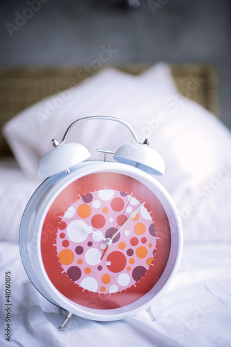 Alarm clock on bed, close-up