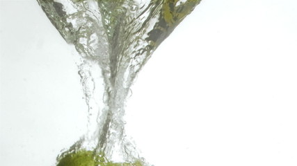 Green pear in super slow motion falling in the water