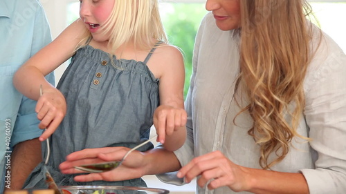 Girl helping her mother make a salad