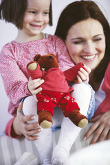 Girl with mother holding teddy bear, smiling