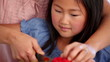 Daughter cutting a red pepper with her mother