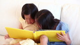 Girl talking to her sister as they read a book together