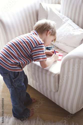 Boy writing on notepad, side view