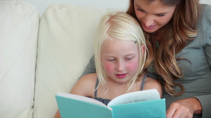 Girl laughing as she reads a book with her mother