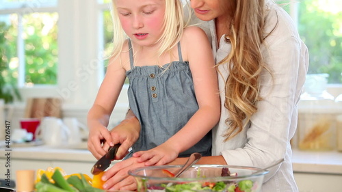 Girl cutting a yellow pepper with her mother