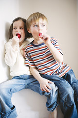 Children eating lollipop, looking away
