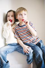 Children eating lollipop, looking away
