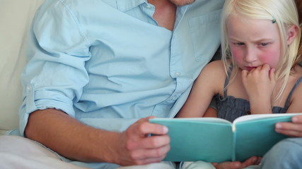 Parents reading a book with their daughter