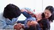 Parents tickling their children