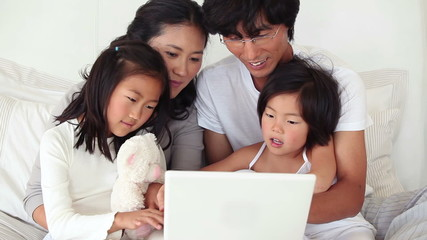 Family sitting together as they use a laptop
