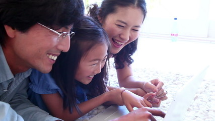 Family laughing while using a laptop