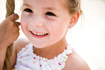Girl holding rope, smiling, close-up