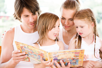 Family looking at picture book, smiling
