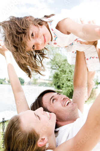 Parents playing with daughter, smiling