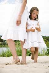 Daughter with mother standing on sand