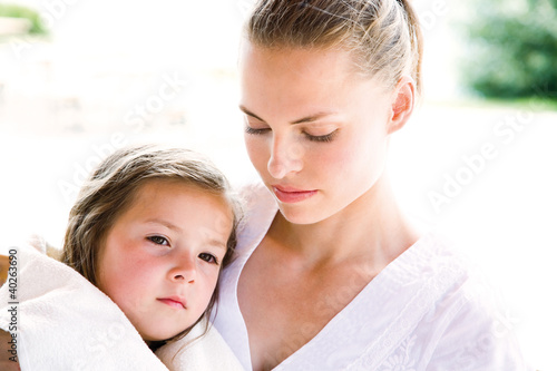 Mother with daughter sitting on bench