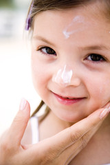 Girl with cream on face, smiling