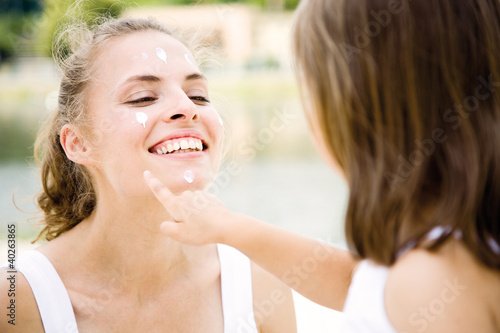 Daughter applying cream on mother's face