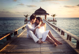 Fototapety Sensual happy couple with white clothes on a pier (Maldives)
