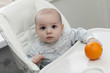 Serious baby with orange