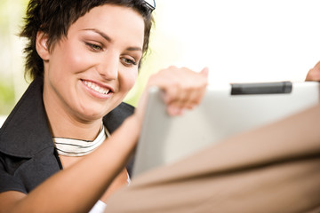 Businesswoman using laptop, smiling