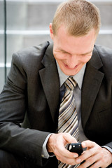 Businessman using mobile phone, smiling