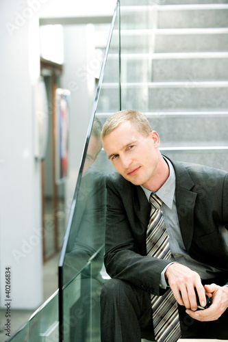 Businessman holding mobile phone, portrait