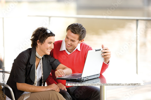 Business people looking at laptop, smiling