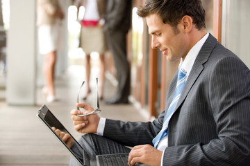 Businessman using laptop, side view