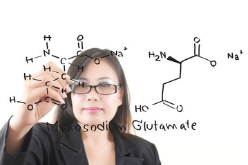 Teacher lady writing scientific formula on the whiteboard.