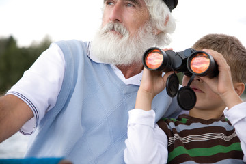 Grandson with grandfather using binoculars