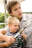 Father with son holding fishing rod