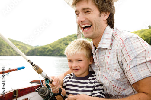Father with son holding fishing rod, smiling