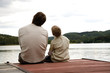 Father with son sitting on pier