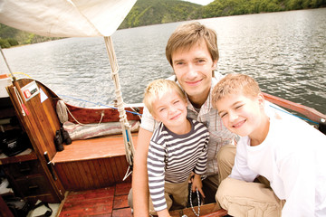 Father with sons on nautical vessel, smiling, portrait