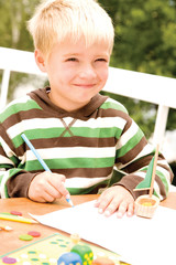 Boy holding pencil, smiling