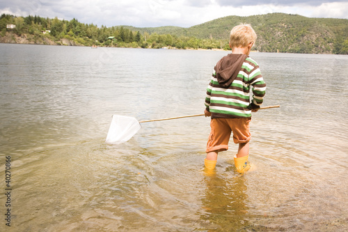 Boy holding fishing net in river