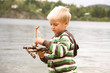 Boy holding twig by river, side view