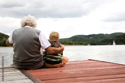 Grandfather sitting with grandson on pier