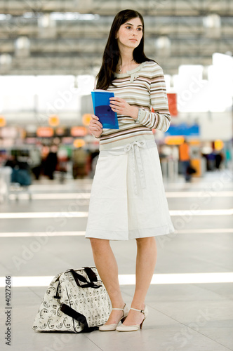 Young woman holding brochure at airport