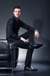Junger sportlicher Mann sitzt auf Sessel Lehne