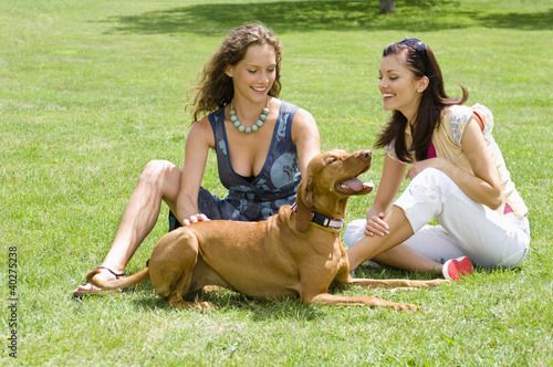 Friends sitting in park with dog