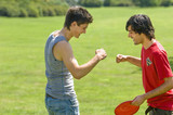 Two young men playing with plastic disc on park
