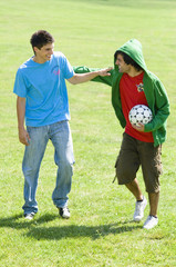 Two young men with soccer ball on park