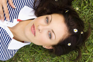 Young woman lying on grass, portrait