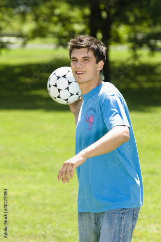 Young man throwing soccer ball in park, portrait